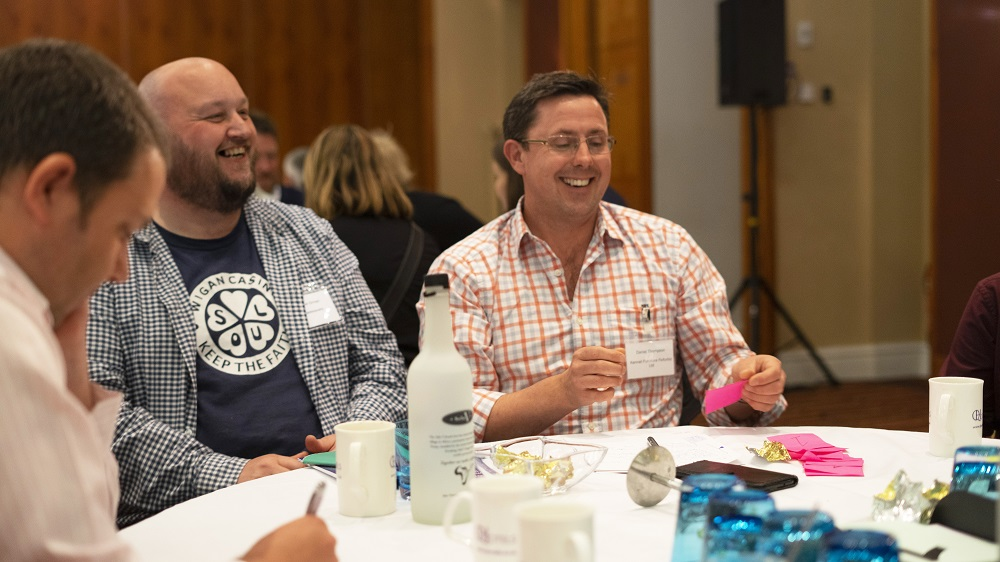 Two men laughing around a table during the reuse network 2019 conference